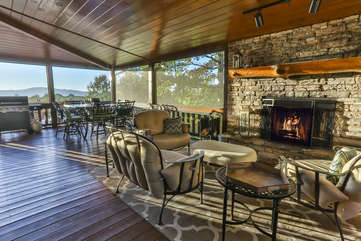 The outdoor fireplace is a beautiful focal point and adds tremendous ambiance to the screen porch. New furnishings now adorn this deck with a added dining table also