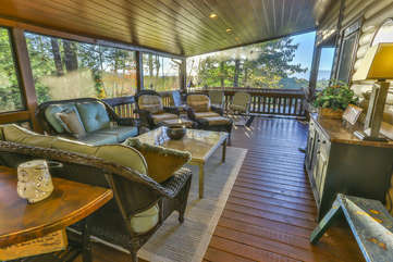 An outdoor rug anchors the furniture pieces and defines the seating area on the side screened in porch.