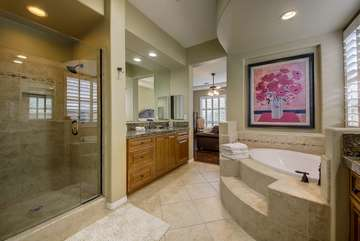 The master bathroom has dual sinks and vanities with granite countertops, an oversize tiled shower, a soaking tub and a walk-in closet.