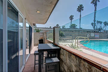 Patio view of pool with table and grill