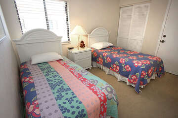 Guest bedroom has twin beds and natural light.