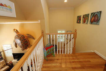 Upper stairwell hallway leading from bedrooms to living area.