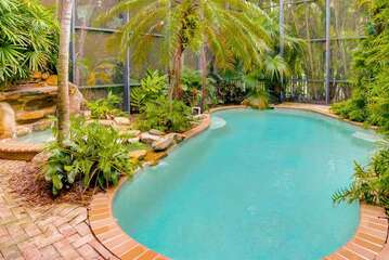Gorgeous tropical pool deck with hot tub waterfall flowing to the heated pool.