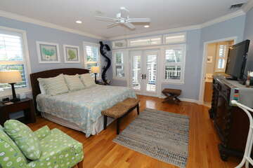 Spacious master bedroom with deck outside.