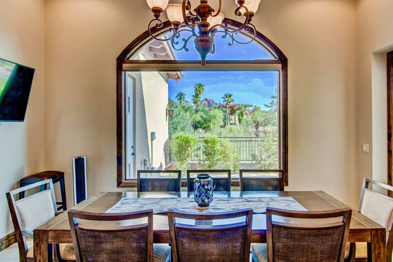 Dinner table with table, chairs, TV on left wall, and window behind with views of desert landscaping.