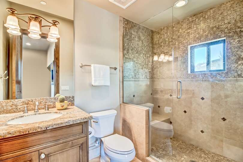 Walk in shower surrounded by granite and imported tile, toilet, and sink with mirror and lighting.