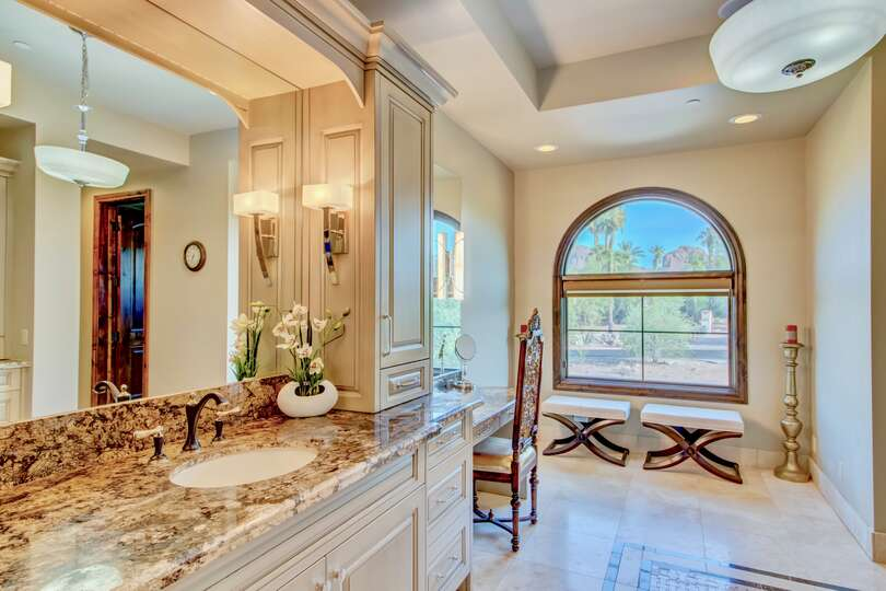 Master bathroom, with large mirror above sink, vanity with chair, and two stools below a large window.