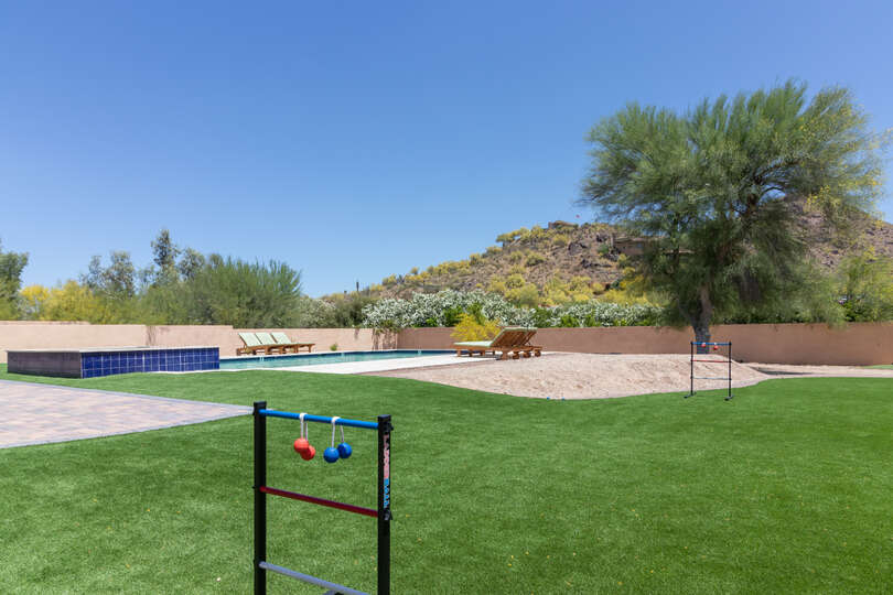 Games, lawn, pool, and sand pit of the back yard.