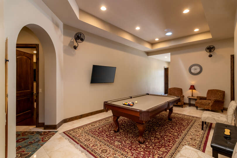 Pool table, TV, and seating in open game room area.