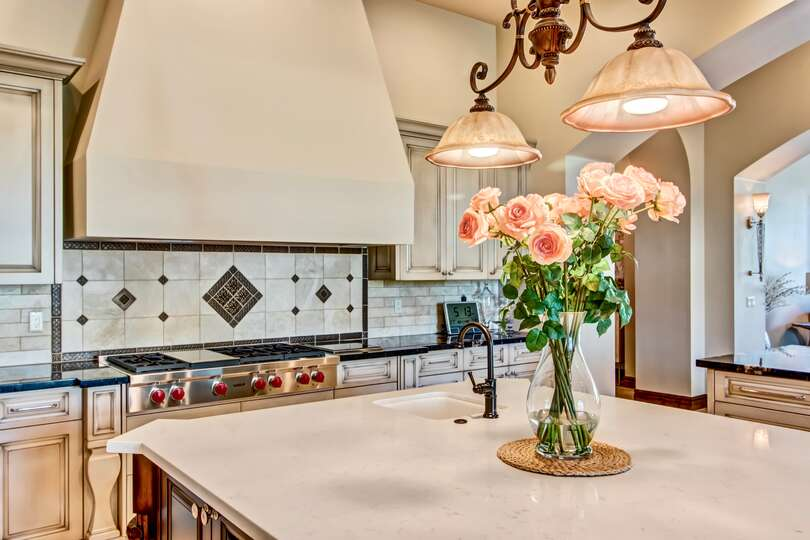 Picture of kitchen with center island (flowers on top), oven, and granite counter-tops.