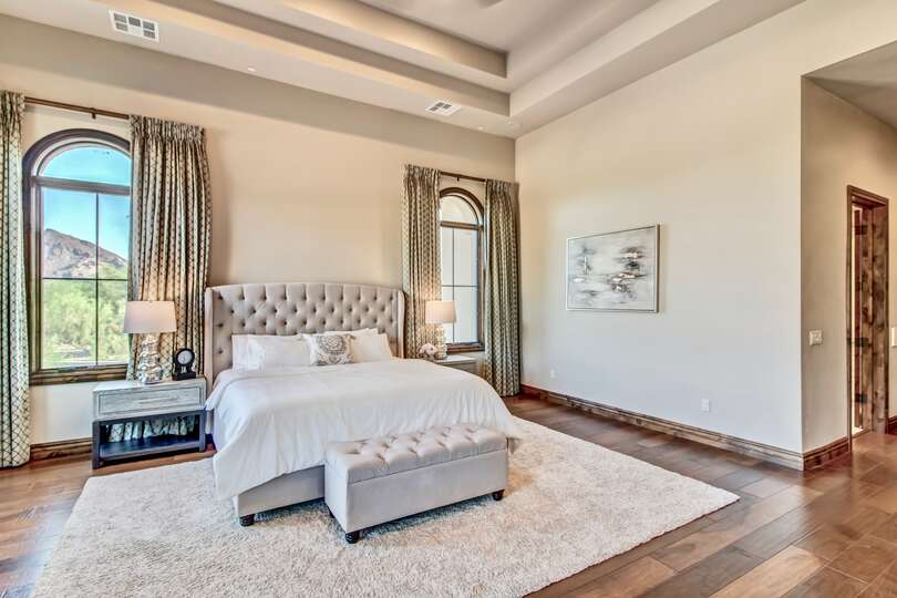 Bed of master bedroom with ottoman at the foot, nightstands with lamps on either side.