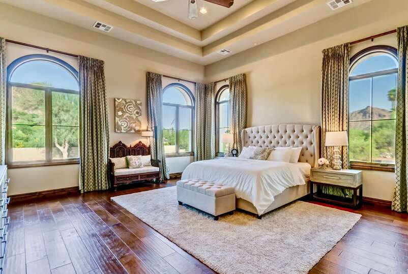 Master bedroom of this vacation home rental in Phoenix, with large open space around the large bed, and open windows looking out over desert landscaping.