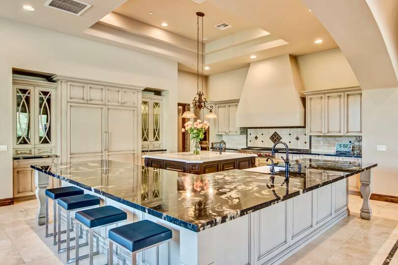 Luxury kitchen of this vacation home rental in Phoenix, with bar seating along a large L-shaped kitchen island with sink, and a small island in the center.