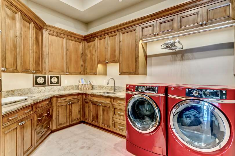 Laundry room of this vacation home rental in Phoenix, with washer, dryer, and sink below the cupboards.