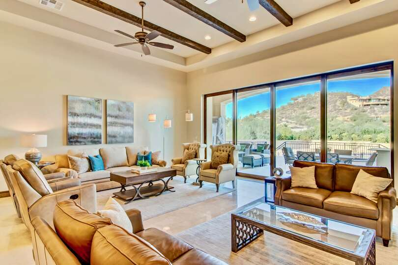 Large living area of this vacation home rental in Phoenix, with multiple couches, coffee tables, and large glass doors opening to the back patio.