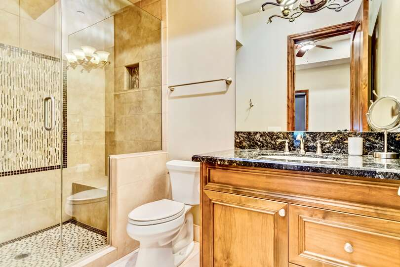 Walk-in shower, toilet, and sink with mirror of bathroom.