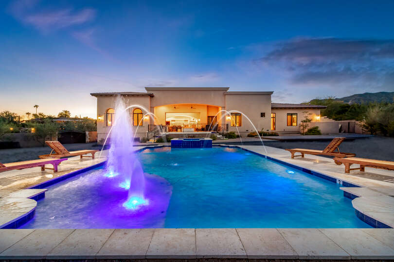 The luxury pool of this vacation home rental in Phoenix, with water features and pool chairs along the sides.