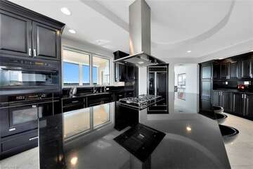 sleek black counter tops and coordinating high end appliances including a gas stove