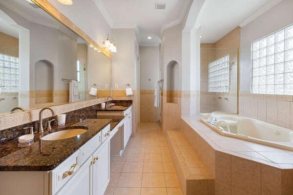 The en suite master bathroom features a luxurious garden bathtub