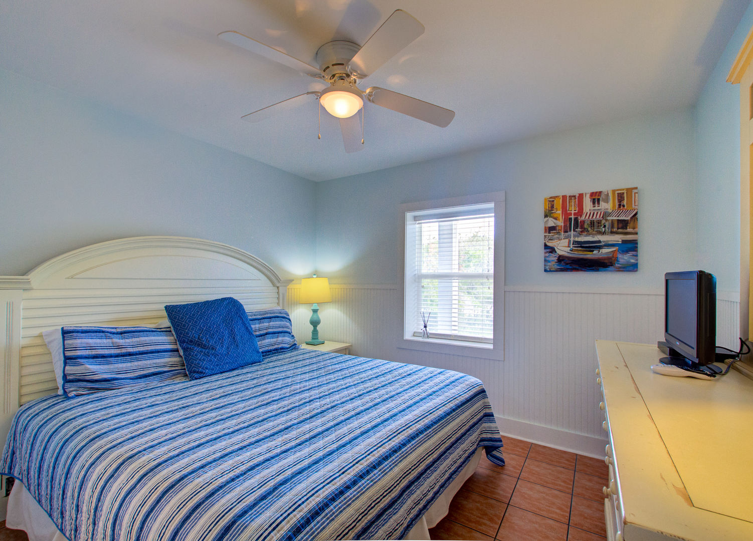 Bedroom with Large Bed, Drawer Dresser, TV, and Ceiling Fan.
