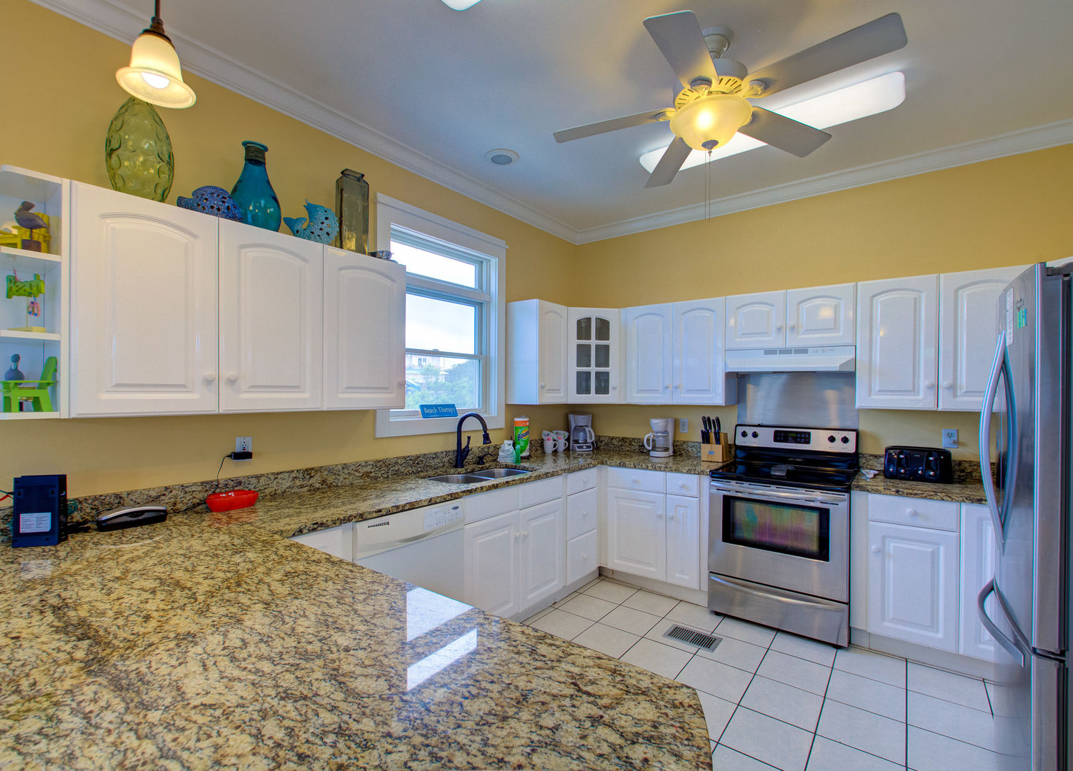 Kitchen with Coffee Makers, Refrigerator, and Ceiling Fan.