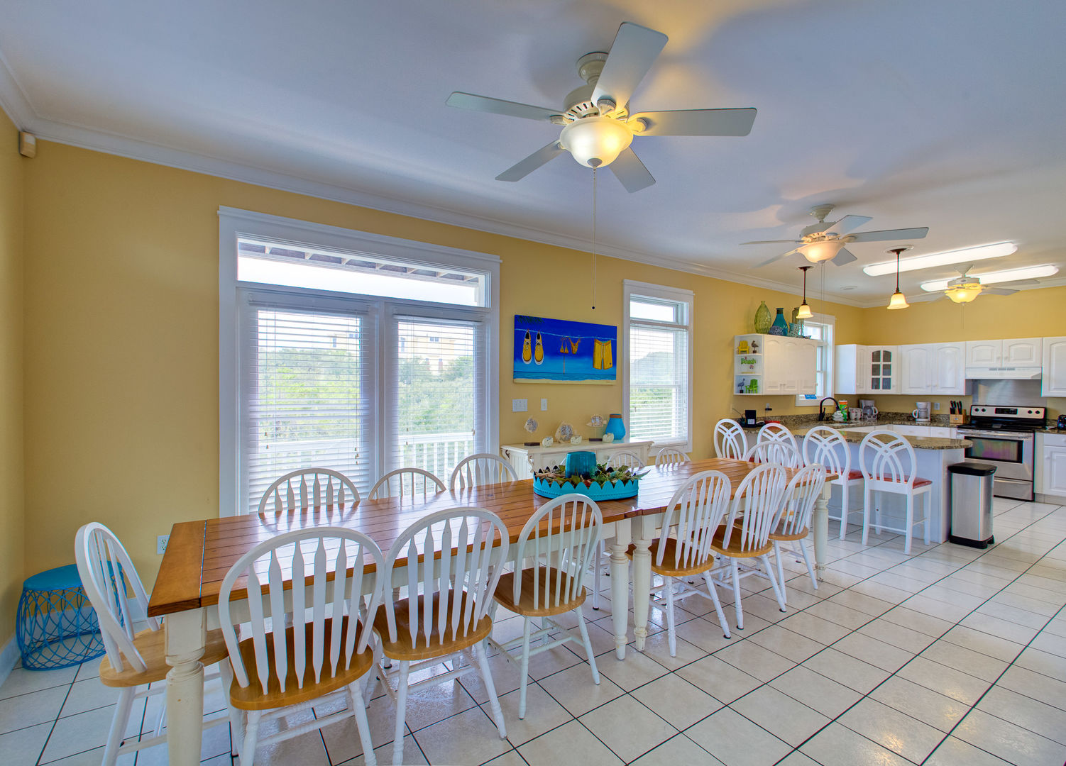 Big Dining Table, Chairs, Kitchen Counter, Stools, Ceiling Fans, and Windows.