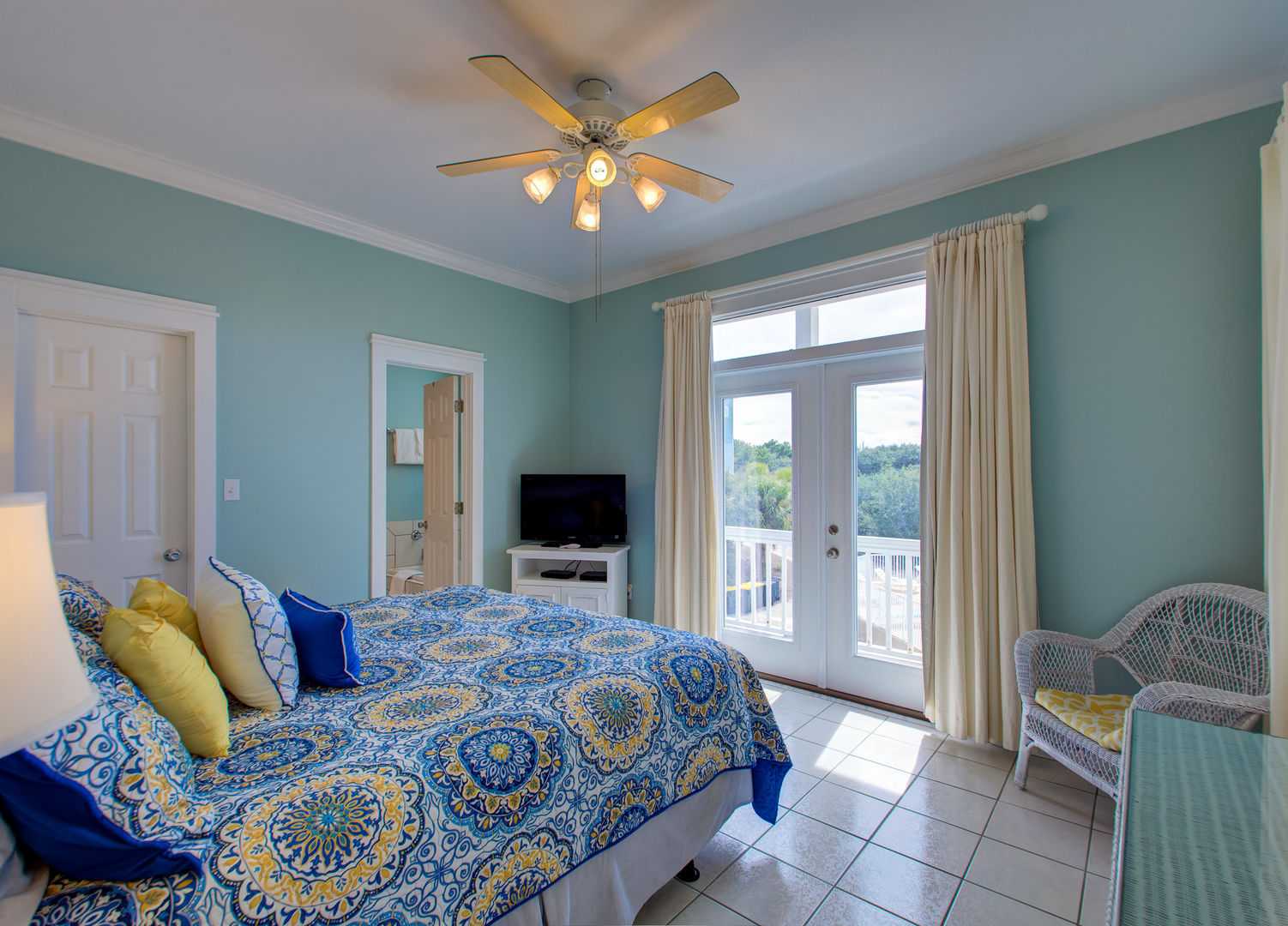Large Bed, Patio Doors to the Balcony, TV, and Ceiling Fan.