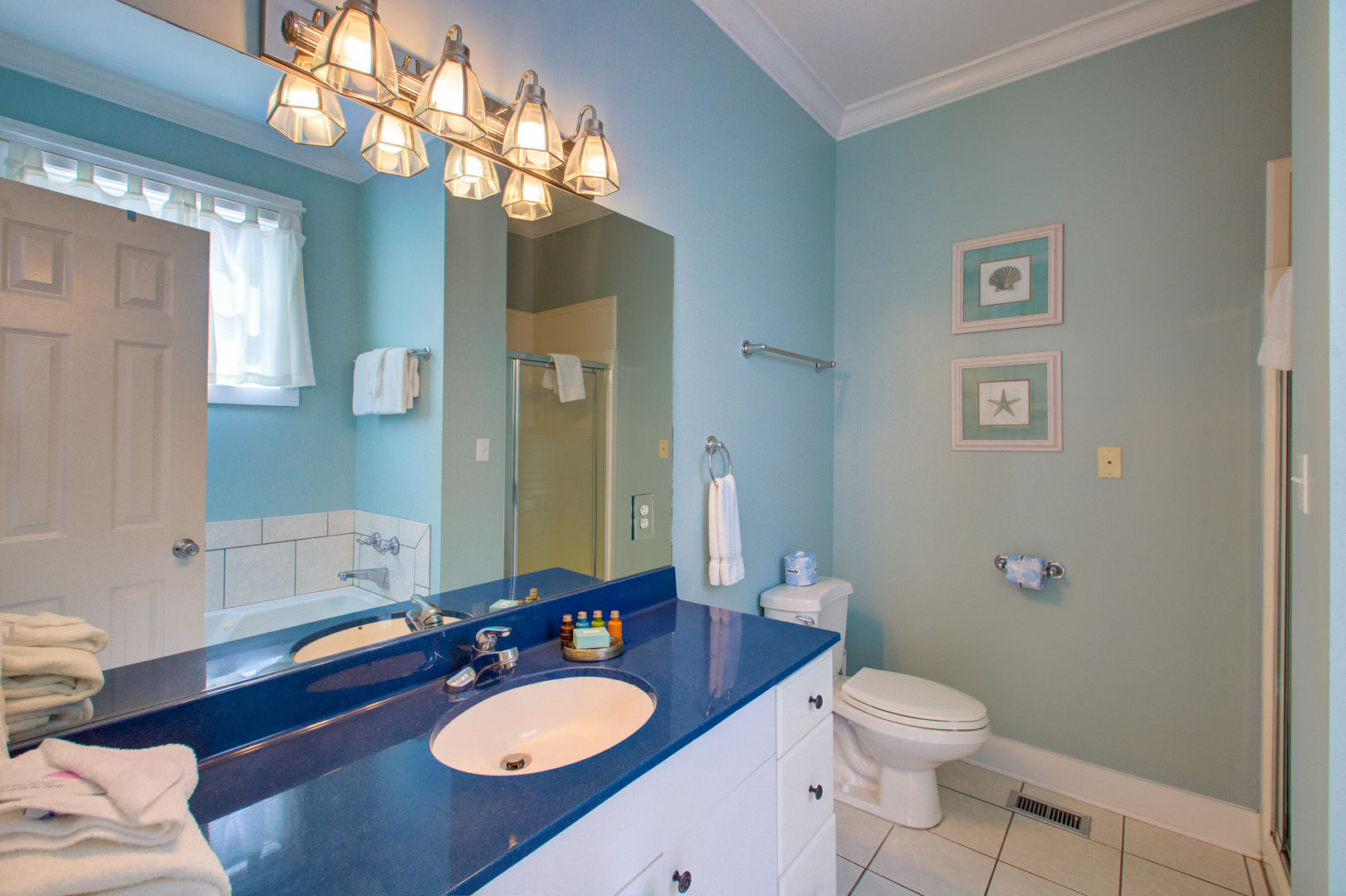 Single Vanity Sink, Mirror, Wall Lamp, and Toilet.