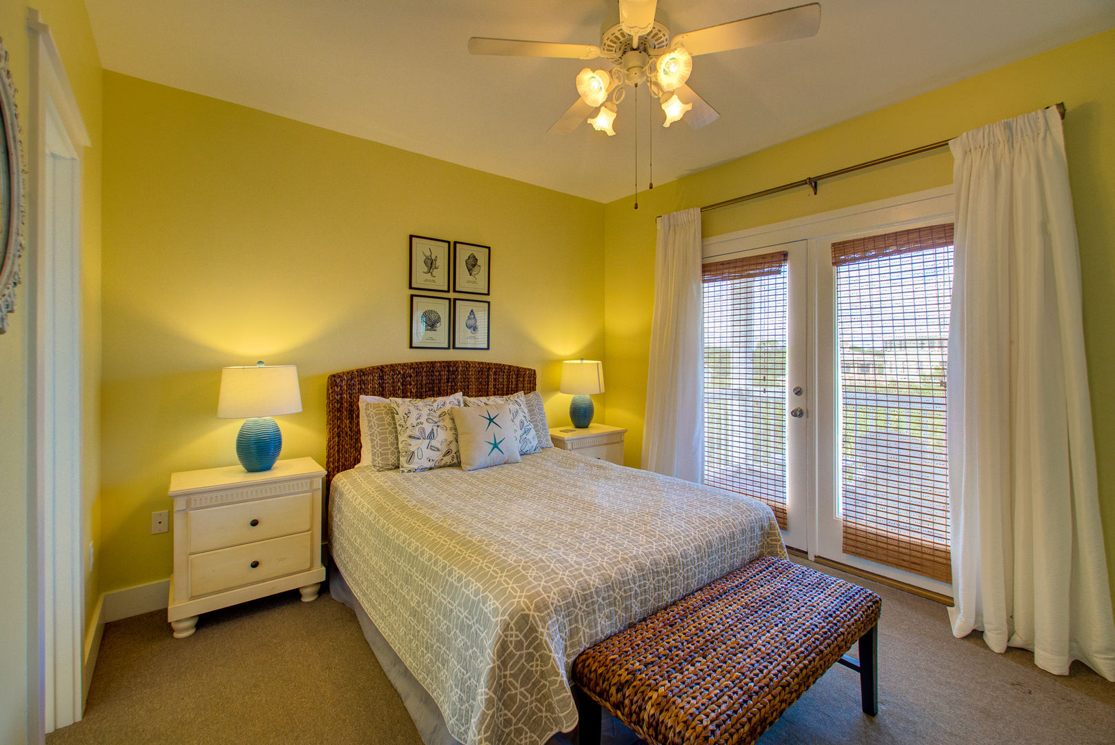Large Bed, Nightstands, Lamps, Doors to the Balcony, and Ceiling Fan.