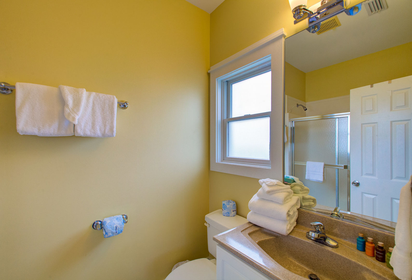 Single Vanity Sink, Mirror, Shower, and Toilet.
