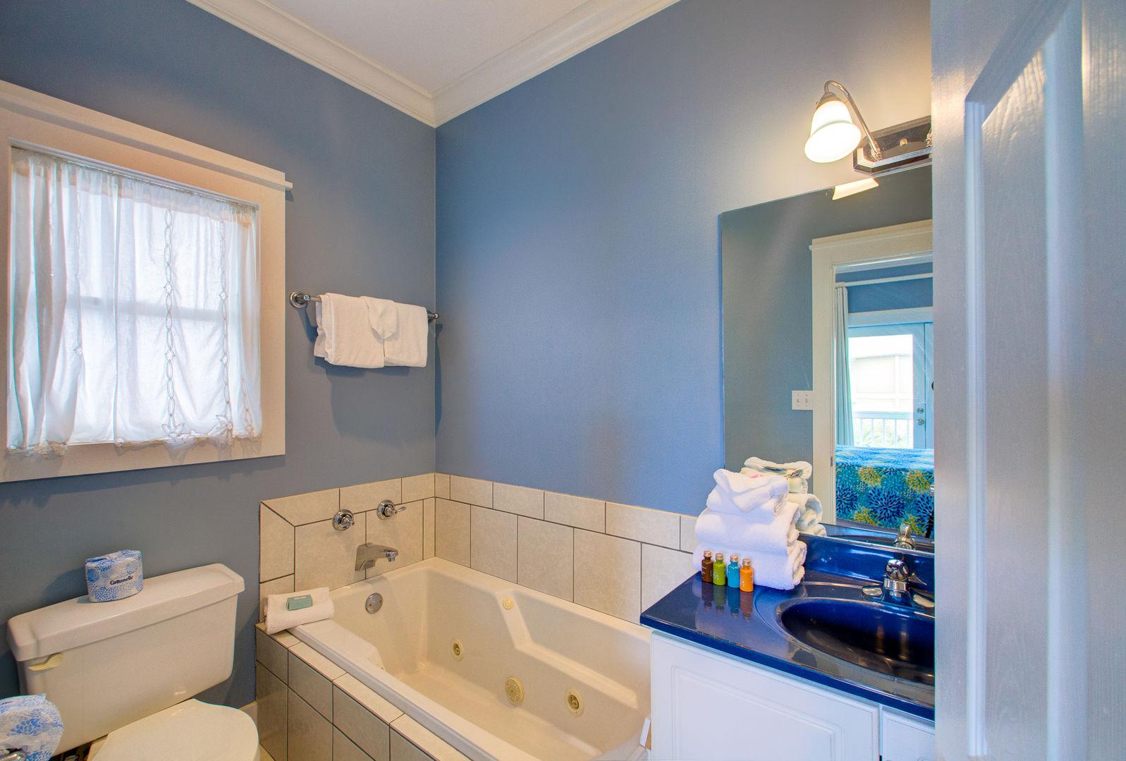 Single Vanity Sink, Mirror, Bathtub, and Toilet.