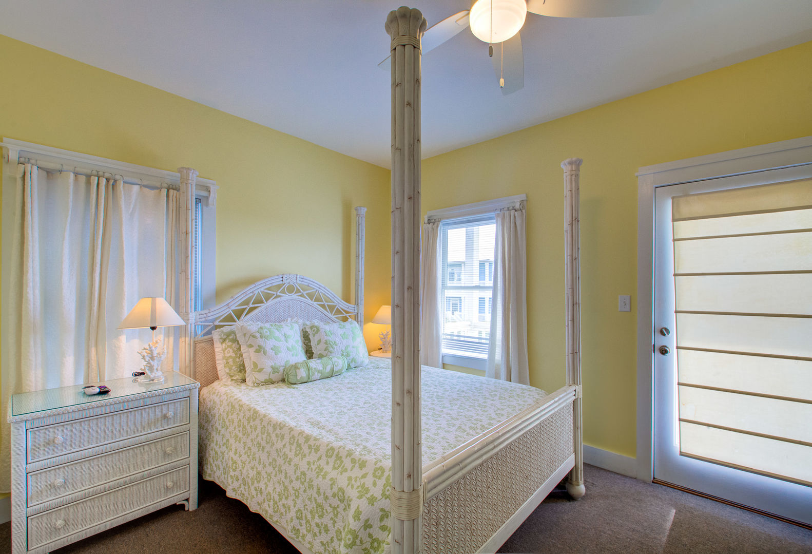 Large Bed, Nightstands, Lamps, Windows, and Door to the Balcony.