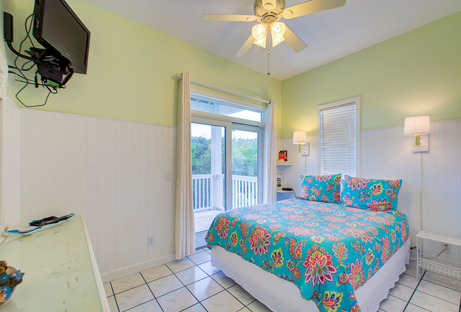 Large Bed, Doors to the Balcony, TV, and Ceiling Fan.