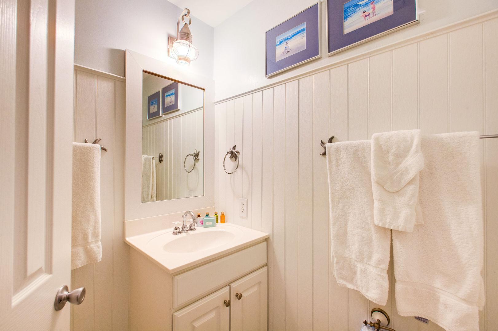 Single Vanity Sink, Mirror, and Towels.