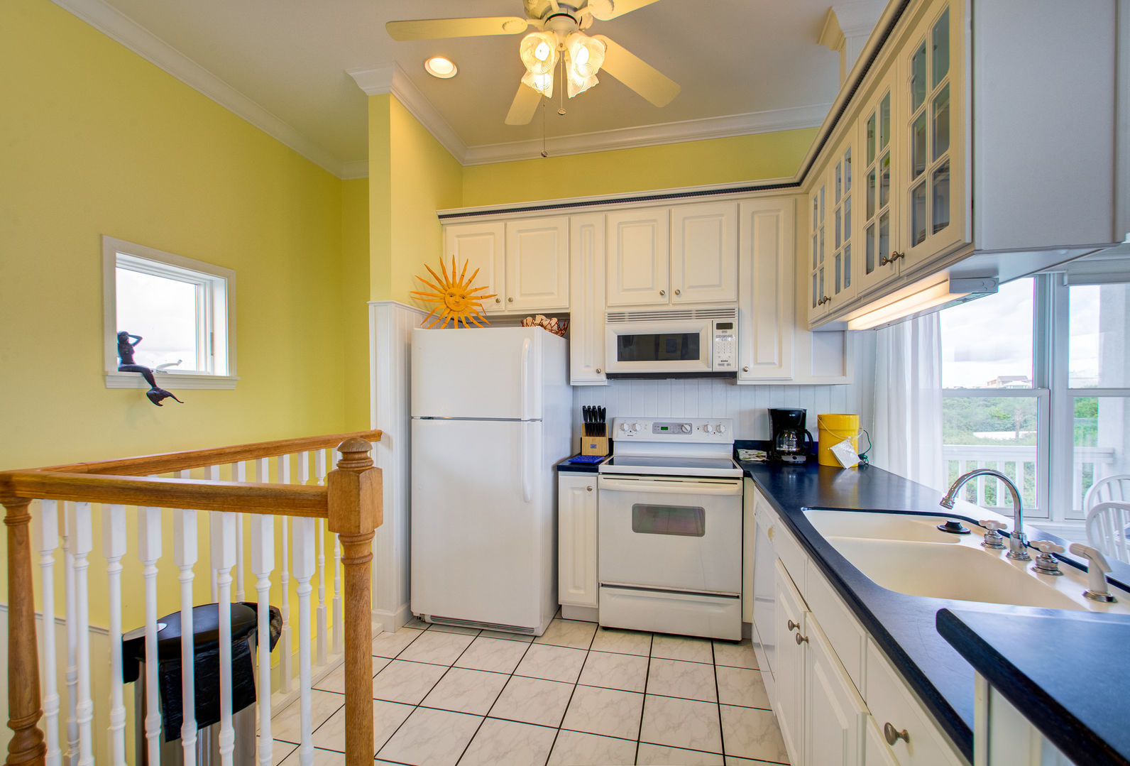 Kitchen with Microwave, Coffee Maker, Refrigerator, and Ceiling Fan.