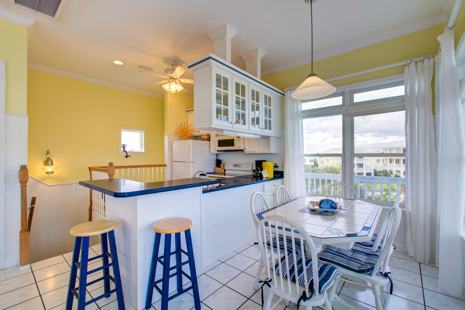 Kitchen with Breakfast Bar, Stools, Dining Table, Chairs, and Windows.