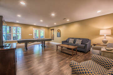 Lower level game room - plenty of seating for all and pool for a fun game night!