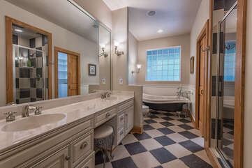 Master en-suite bath. Checkered floor, double sinks, stand alone shower & soaking tub with shower handle.