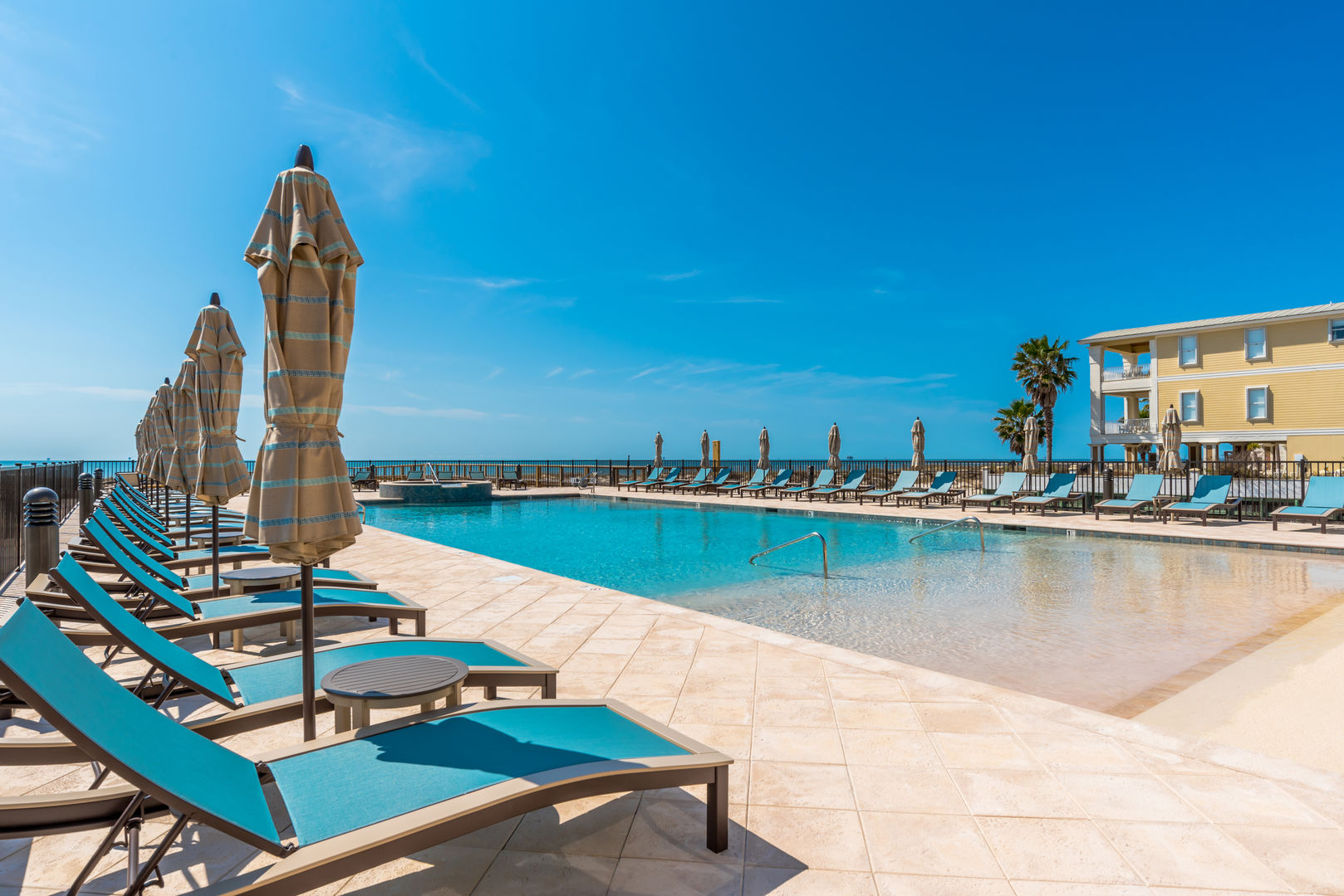 Image of Lounge Chairs and Umbrellas by Pool.