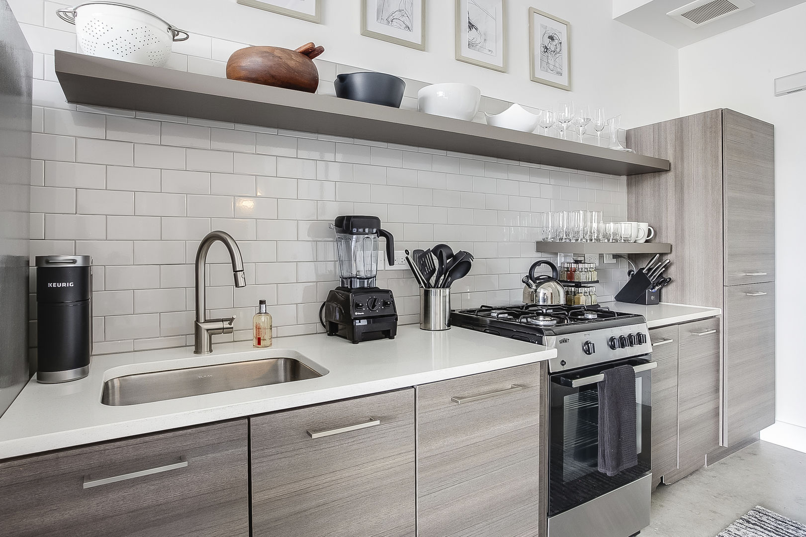 The kitchen of this Ponce City Market rental with modern appliances and a deep sink.