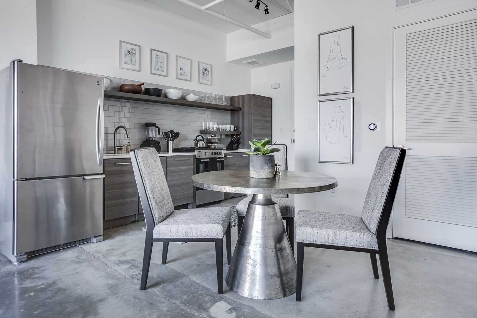 Dining area and kitchen of this Ponce City Market rental with modern appliances and a table for three.