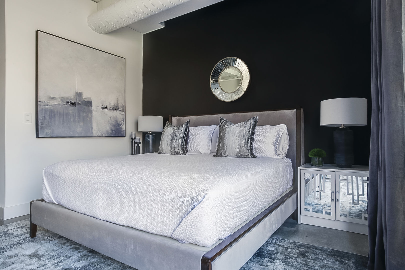 The sleeping area of this Ponce City Market rental with large bed and nightstands.