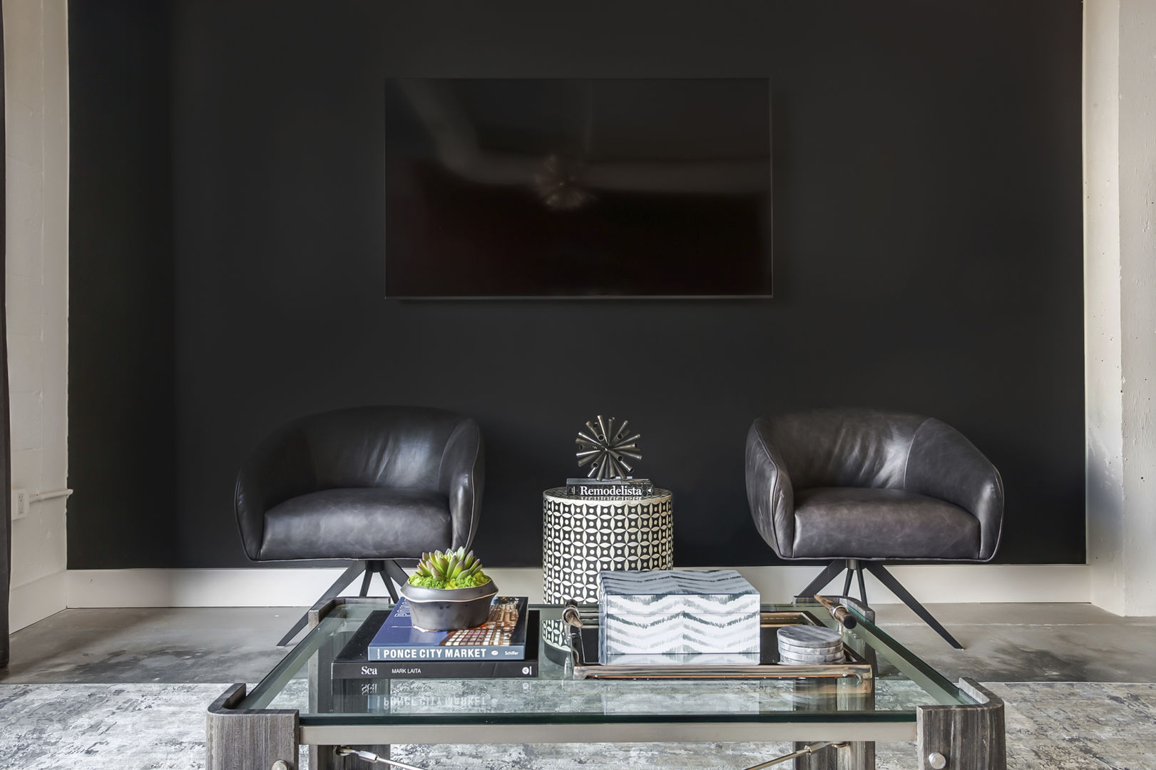 Wall-mounted TV rests above two leather armchairs in this Ponce City Market rental, and in front of a coffee table.