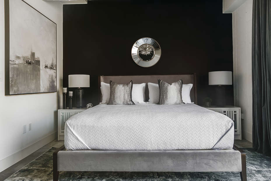 Sleeping area with a large, decorative bed between a pair of nightstands.