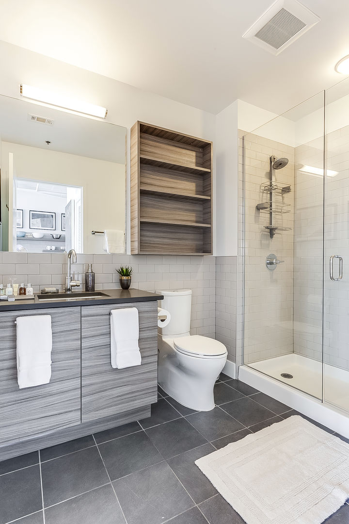 Bathroom of this Ponce City Flat with vanity sink, toilet, and walk-in shower.
