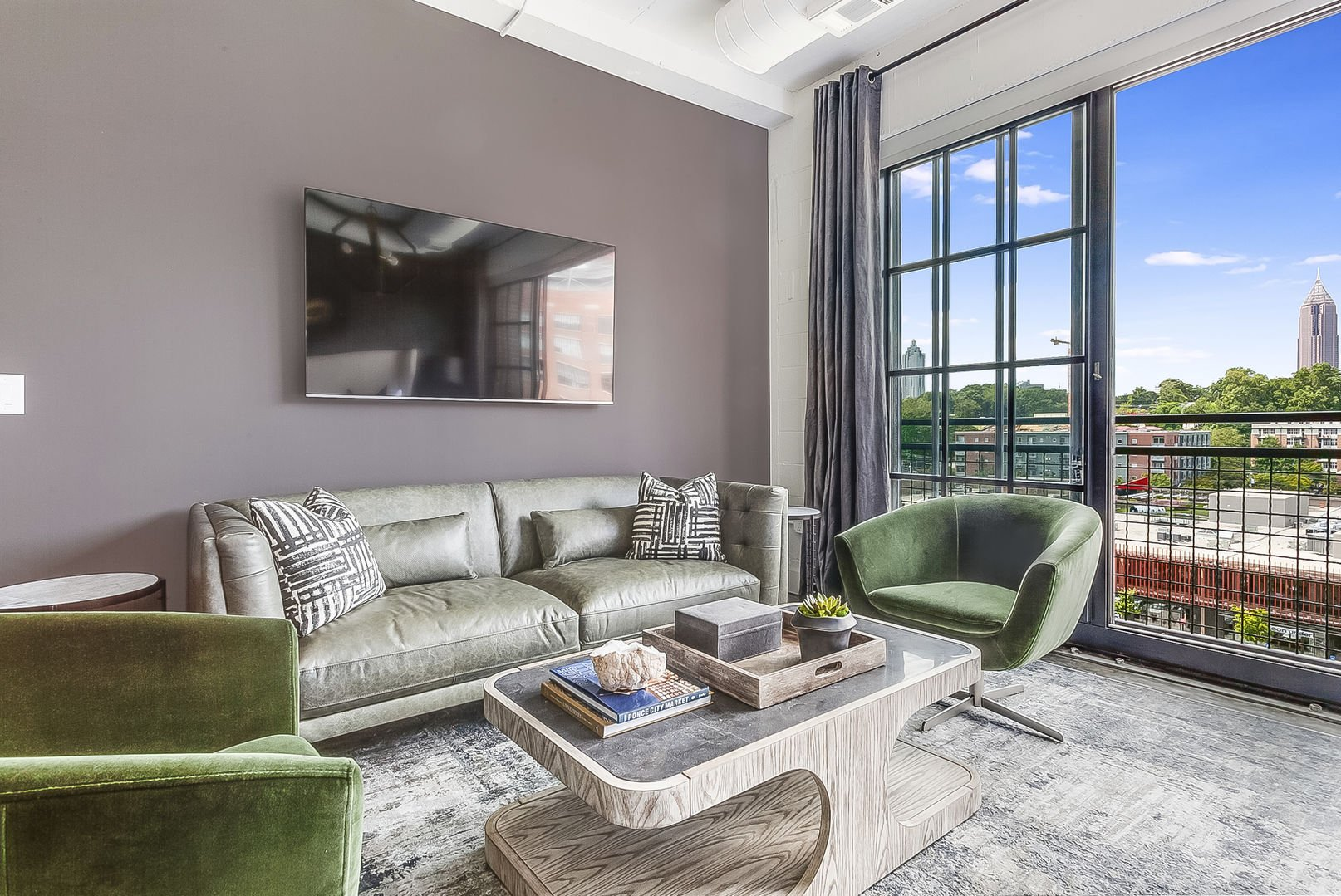 Living area of this Ponce City Flat, with a wall-mounted TV, sofa, armchairs, and coffee table in front of a large open window.
