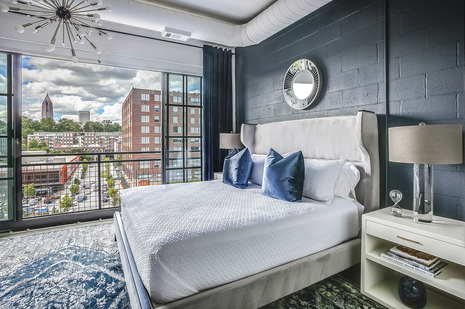 Sleeping area with a large bed, two nightstands, and an open window overlooking the city.