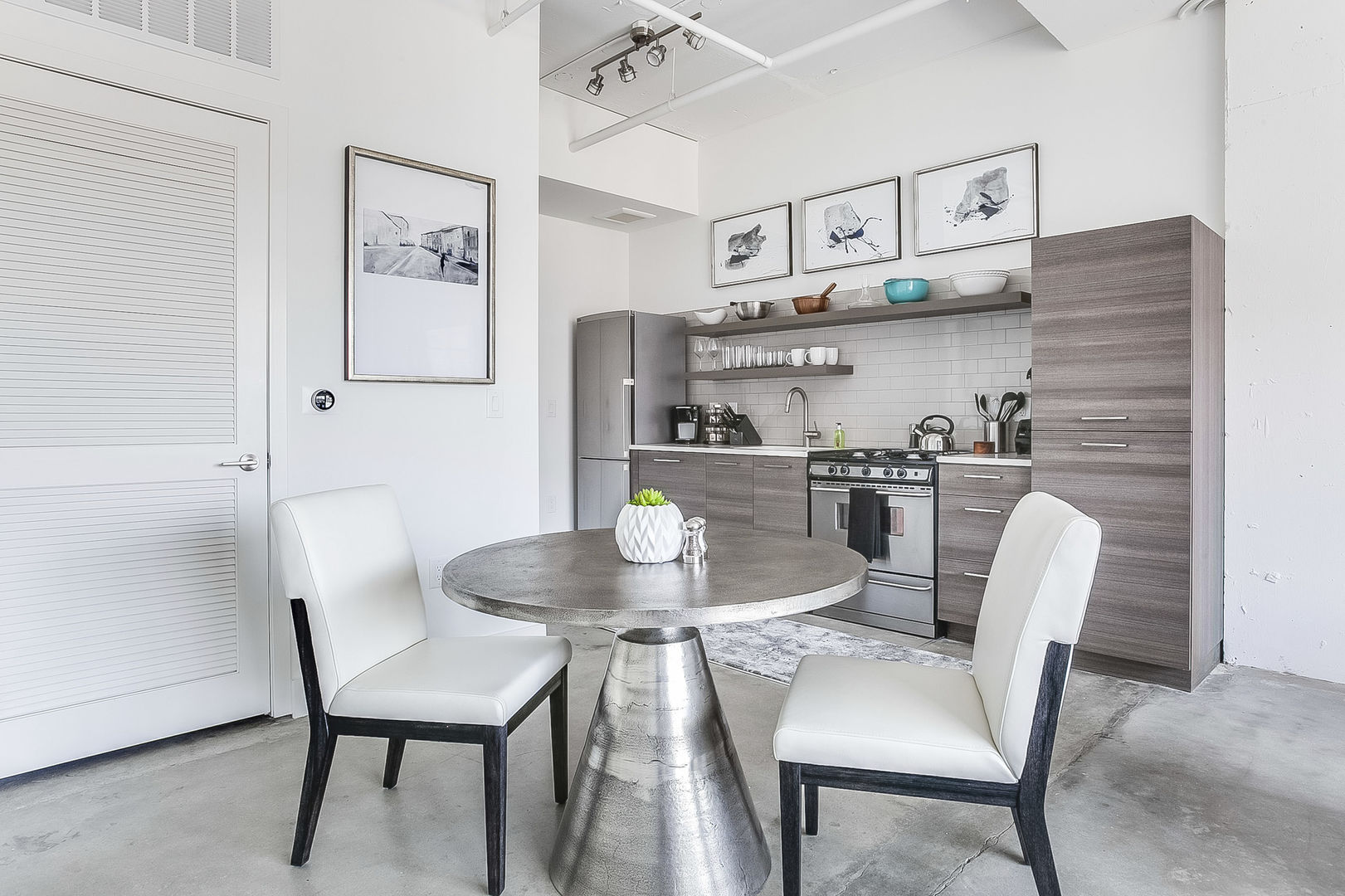 Dining area of this Apartment Near Ponce City Market, with the kitchen in the background.