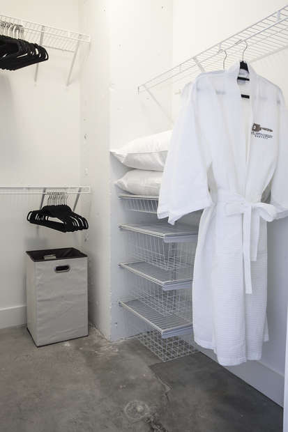 Closet with a robe hanging in it.