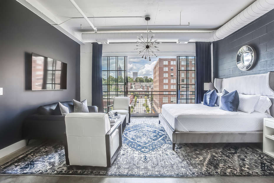 Living/Sleeping area of this Apartment Near Ponce City Market, complete with large bed, sofa, armchairs, and a small table in front of a large open window.